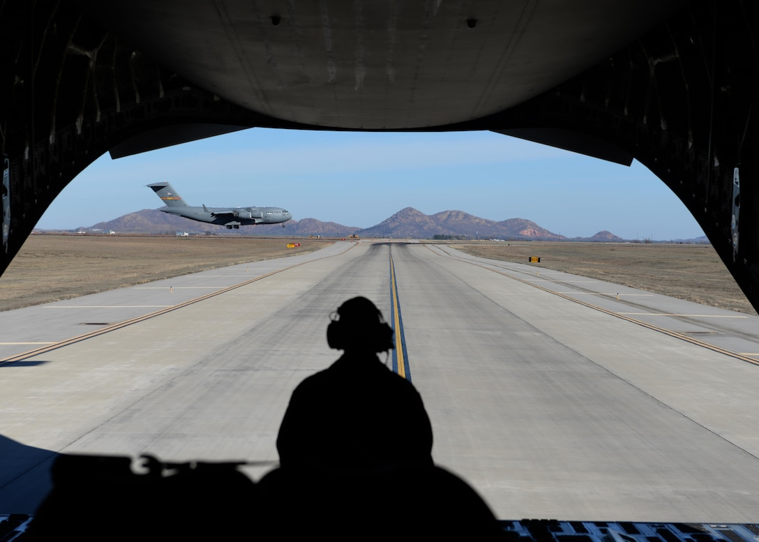 Tech. Sgt. Donnie McCorkle watches a C-17Globemaster III land, Feb. 12, 2015, at Altus Air Force Base, Okla. McCorkle is a C-17 loadmaster and was preparing for a combat off-load, where cargo is pushed out of the cargo door while the aircraft is taxiing. This demonstration was a part of a familiarization flight to help air traffic controllers understand what aircrews do and how important it is to maintain communication between the aircraft and control tower. (U.S. Air Force photo/Airman 1st Class Nathan Clark)