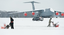 A C-5M Super Galaxy sits on the flightline as Airmen clear snow Feb. 17, 2015, on Dover Air Force Base, Del. Winter Storm Octavia dumped a total of four inches of snow on the base and throughout the local area. (U.S. Air Force photo/Roland Balik)