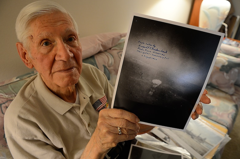 Russell Gackenbach, the navigator aboard the B-29 Superfortress, Necessary Evil, during the nuclear bombing mission over Hiroshima, japan on Aug. 6, 1945, shows a photo he took during the historic day, Clearwater, Fla., Feb 10, 2015.  Gackenbach is the last surviving member from the mission. (U.S. Air Force photo by Tech. Sgt. Brandon Shapiro/Released).