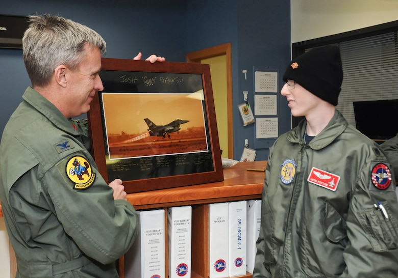"Col. Rick Poplin, 138th Operations Group (OG) Commander presents ""pilot for a day"" Josh Payton with a token of his appreciation for visiting as an honored guest Feb. 19, 2015, at the Tulsa Air National Guard base, Tulsa, Okla.  The pilot for a day program is intended to recognize and honor children with potentially life threatening illnesses and started at the 138th in May 2012, and has hosted seven children since it began.  (U.S. National Guard photo by Senior Master Sgt.  Preston L. Chasteen/Released)"