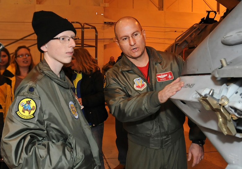 "- Josh Payton, the 138th Fighter Wing's ""pilot for a day"" is briefed on the operations of an F-16 by Maj. Michael ""Deuce"" Scorsone Feb. 19, 2015, at the Tulsa Air National Guard base, Tulsa, Okla.  The pilot for a day program is intended to recognize and honor children with potentially life threatening illnesses and started at the 138th in May 2012, and has hosted seven children since it began.  (U.S. National Guard photo by Senior Master Sgt.  Preston L. Chasteen/Released)"