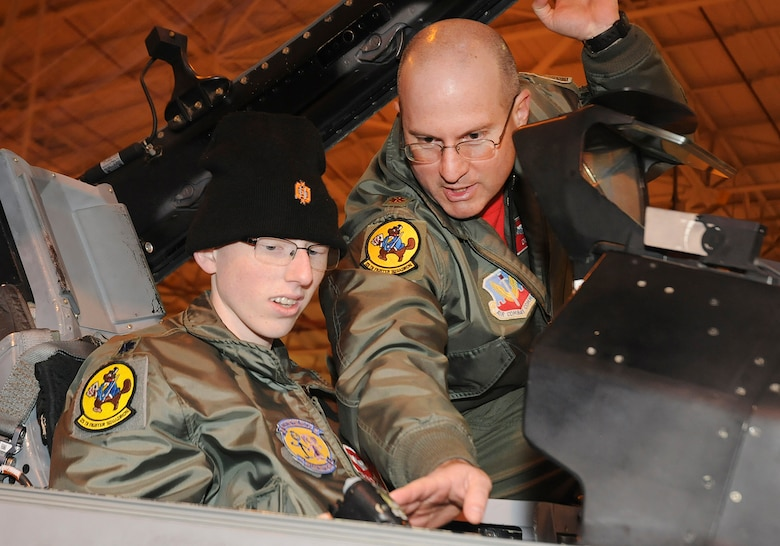 "Josh Payton, the 138th Fighter Wing's ""pilot for a day"" is briefed on the cockpit functionality of an F-16 by Maj. Michael ""Deuce"" Scorsone Feb. 19, 2015, at the Tulsa Air National Guard base, Tulsa, Okla.  The pilot for a day program is intended to recognize and honor children with potentially life threatening illnesses and started at the 138th in May 2012, and has hosted seven children since it began.  (U.S. National Guard photo by Senior Master Sgt.  Preston L. Chasteen/Released)"