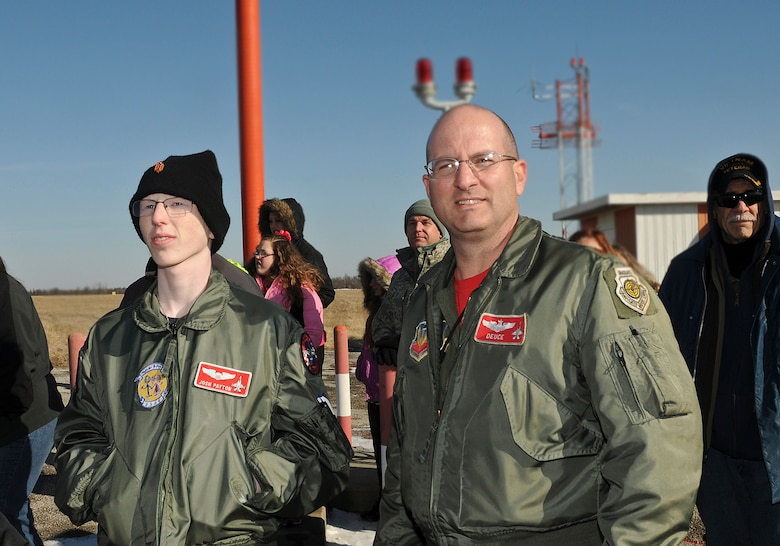 "Josh Payton, the 138th Fighter Wing's ""pilot for a day"" and Maj. Michael ""Deuce"" Scorsone watch F-16's take off near the runway Feb. 19, 2015, at the Tulsa Air National Guard base, Tulsa, Okla.  The pilot for a day program is intended to recognize and honor children with potentially life threatening illnesses and started at the 138th in May 2012, and has hosted seven children since it began.  (U.S. National Guard photo by Senior Master Sgt.  Preston L. Chasteen/Released)"