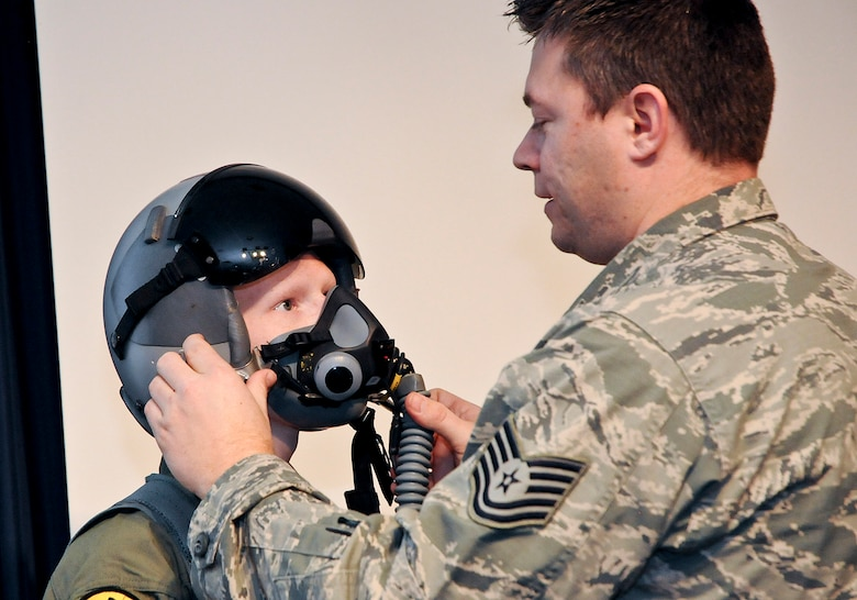 "Aircrew Flight Equipment Technician, Tech. Sgt. Craig Michael adjusts a helmet for an honored guest of the 138th Fighter Wing and ""pilot for a day"" Josh Payton Feb. 19, 2015, at the Tulsa Air National Guard base, Tulsa, Okla.  The pilot for a day program is intended to recognize and honor children with potentially life threatening illnesses and started at the 138th in May 2012, and has hosted seven children since it began.  (U.S. National Guard photo by Senior Master Sgt.  Preston L. Chasteen/Released)"