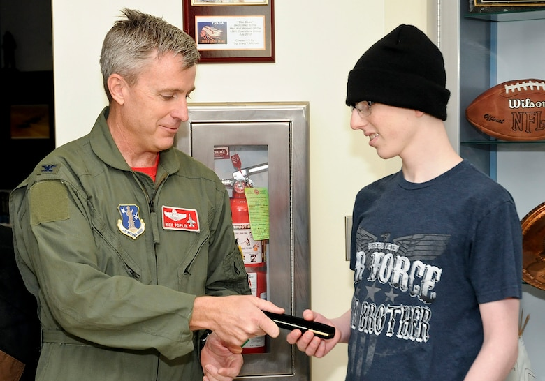 """Col. Rick Poplin, 138th Operations Group (OG) Commander presents """"pilot for a day"""" Josh Payton with the keys to the OG during his visit as an honored guest Feb. 19, 2015, at the Tulsa Air National Guard base, Tulsa, Okla.  The pilot for a day program is intended to recognize and honor children with potentially life threatening illnesses and started at the 138th in May 2012, and has hosted seven children since it began.  (U.S. National Guard photo by Senior Master Sgt.  Preston L. Chasteen/Released)"""