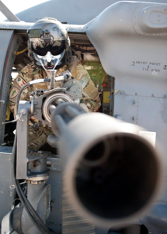 U.S. Air Force Master Sgt. Antonio Jimenez, 303rd Expeditionary Rescue Squadron special mission aviator, simulates 'stand ready' with the GAU-2 mini-gun at Camp Lemonnier, Djibouti on Jan. 26, 2015. This position is taken if and when they need to provide combat air support during any rescue mission. (U.S. Air Force photo by Staff Sgt. Kevin Iinuma)