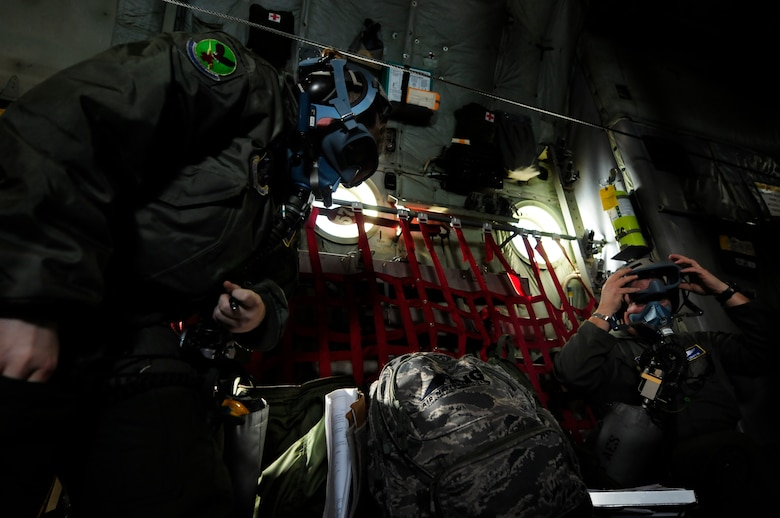 U.S. Air Force Senior Airman Brittany Callahan (left) and 1st Lt. Shawn Griffin (right) don oxygen masks as part of an emergency procedure during a scenario on an aeromedical training mission roundtrip from North Carolina Air National Guard Base, Charlotte Douglas Intl. Airport, Jan. 9, 2015. The training mission scenario is to transfer patients from Landstuhl Medical Center, Germany, to Malcolm Grove Medical Center, Md. (U.S. Air National Guard photo by Staff Sgt. Julianne M. Showalter, 145th Public Affairs/ Released)