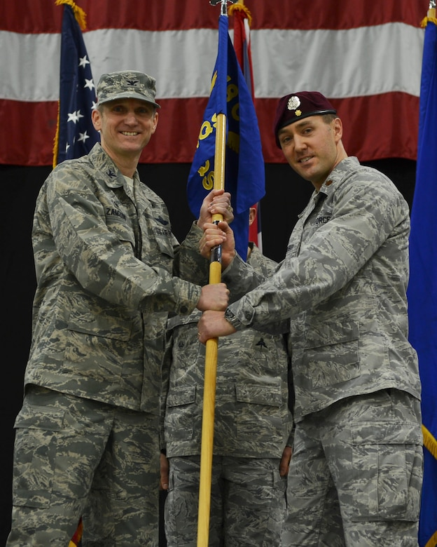 Col. Scottie Zamzow, 48th Operations Group commander, presents command of the 57th Rescue Squadron to Maj. Patrick Gruber at Royal Air Force Lakenheath, England, Feb. 18, 2015. The passing of the guidon is a representation of the unit's command role. (U.S. Air Force photo by Airman 1st Class Dawn M. Weber/Released)