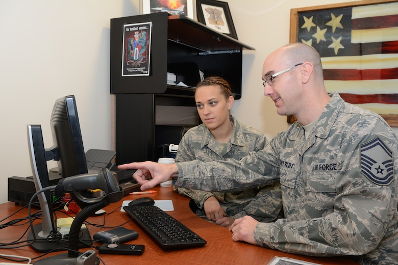 Senior Master Sgt. Craig A. Mortvedt, personnel superintendent for the Wisconsin Air National Guard's 115th Fighter Wing in Madison, Wis. instructs Senior Airman Amanda Lafke on the use of the Defense Enrollment Eligibility Reporting System Feb.8, 2015.(U.S. Air National Guard photo by Tech. Sgt.Tiffany Black)