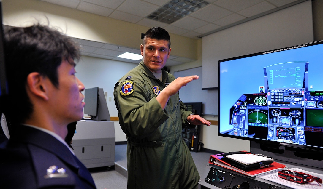 U.S. Air Force Capt. Ezekiel Duran, 18th Aerospace Medicine Squadron aerospace and operational physiologist, explains to Japan Air Self-Defense Force Capt. Makoto Inada, 4th Division, Aeromedical Laboratory flight surgeon, how to operate the Reduced Oxygen Breathing Device on Kadena Air Base, Japan, Feb. 12, 2015. Five JASDF personnel from the 4th Division, Aeromedical Laboratory, Iruma Air Base, Saitama, visited Kadena to learn how the U.S. Air Force conducts physiology refresher training without the need for an altitude chamber. (U.S. Air Force photo by Naoto Anazawa)