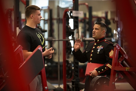 Shane Lemieux (left), a senior at West Valley High School in Yakima, Washington, speaks with local Marine recruiter Sgt. James Campos prior to receiving a Semper Fidelis All-American Bowl game certificate in the school's weight room Feb. 18, 2015. Lemieux, a highly-touted offensive guard, was one of three Washington State football players selected to play in the January 4 game in Carson, California. Following his high school graduation, Lemieux will attend the University of Oregon on an athletic scholarship. (U.S. Marine Corps photo by Sgt. Reece Lodder)