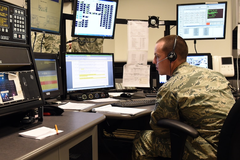 Staff Sgt. Adam Hughes, 460th Security Forces Squadron Base Defense Operations Center controller, monitors base security Feb. 19, 2015, during the new BDOC ribbon cutting ceremony on Buckley Air Force Base, Colo. The BDOC ribbon cutting ceremony took place to recognize the new BDOC being opened in the 460th SFS building. (U.S. Air Force Photo by Airman 1st Class Emily E. Amyotte/Released)
