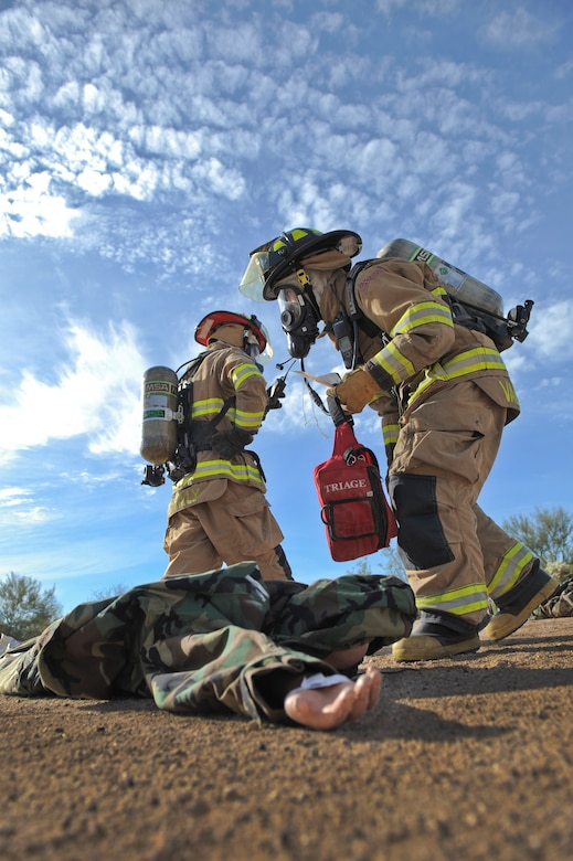 U.S. Air Force Senior Airman Elson Valencia and Capt. Michael Reilly, 355th Civil Engineering Squadron firefighters, triage a simulated victim during a downed aircraft exercise at Davis-Monthan Air Force Base, Ariz., Feb. 19, 2015. D-M was evaluated by the Inspector General's office to ensure the agencies' response was effective and timely. (U.S. Air Force photo by Airman 1st Class Chris Drzazgowski/Released)