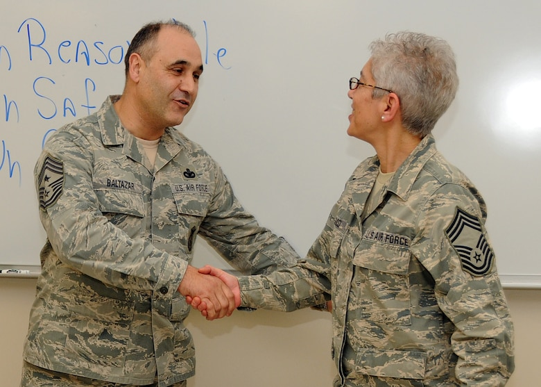 Command Chief Master Sergeant Jose Baltazar, Command Chief, 143d Airlift Wing, Rhode Island Air National Guard, presents Chief Master Sergeant Lorraine Casucci, Military Personnel Management Officer, RIANG, with a challenge coin for her role in preparing for, executing and instructing at the inaugural Leadership Development Course held at Quonset Air National Guard Base, North Kingstown, Rhode Island on January 21, 2015. National Guard Photo by Master Sergeant Janeen Miller (RELEASED)