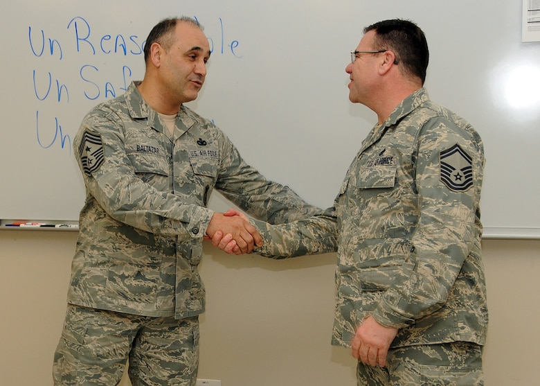 Command Chief Master Sergeant Jose Baltazar, Command Chief, 143d Airlift Wing, Rhode Island Air National Guard, presents Senior Master Sergeant Joseph Hart, Human Resource Advisor, 143d AW, with a challenge coin for his role in preparing for, executing and instructing at the inaugural Leadership Development Course held at Quonset Air National Guard Base, North Kingstown, Rhode Island on January 21, 2015. National Guard Photo by Master Sergeant Janeen Miller (RELEASED)