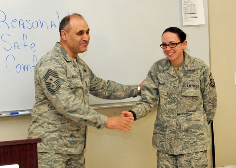 Command Chief Master Sergeant Jose Baltazar, Command Chief, 143d Airlift Wing, Rhode Island Air National Guard, presents Master Sergeant Janeen Miller, Public Affairs Manager, 143d AW, with a challenge coin for her role in preparing for, executing and instructing at the inaugural Leadership Development Course held at Quonset Air National Guard Base, North Kingstown, Rhode Island on January 21, 2015. National Guard Photo by Senior Master Sergeant Brian Robitaille