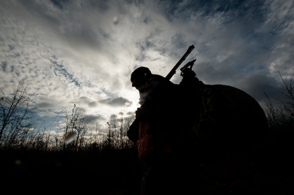 Chaplain Capt. Matthew Spencer walks through a field to his hunting stand Dec. 14, 2014, at Little Rock Air Force Base, Ark. Spencer's hunt was unsuccessful at yielding game this rainy morning. (U.S. Air Force photo by Senior Airman Kaylee Clark)