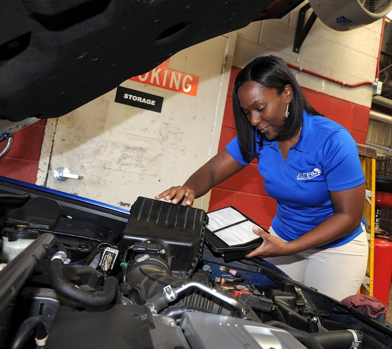 Monique Brisson checks the condition of her car's air filter at the base Auto Hobby Shop.  (U.S. Air Force photo by Tommie Horton)