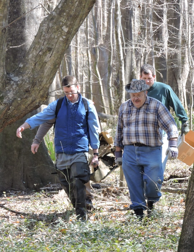 Paul, assisted by museum curator Mike Rowland (in blue) and museum volunteers Arthur Sullivan and Jeff Brett, carry a propeller from the crash site, Feb. 11, 2015. (U.S. Air Force photo by Roland Leach)