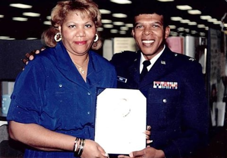 "Col. Joseph C. Ramsey presents a certificate to Margaretta ""Gretta"" Burroughs in an undated photo. Ramsey was the first and only African-American commander at the Air Reserve Personnel Center when it was previously located at the former Lowry Air Force Base, Colorado. He served as the 21st ARPC commander from May 16, 1987 until Aug. 23, 1991. (U.S. Air Force courtesy photo)"