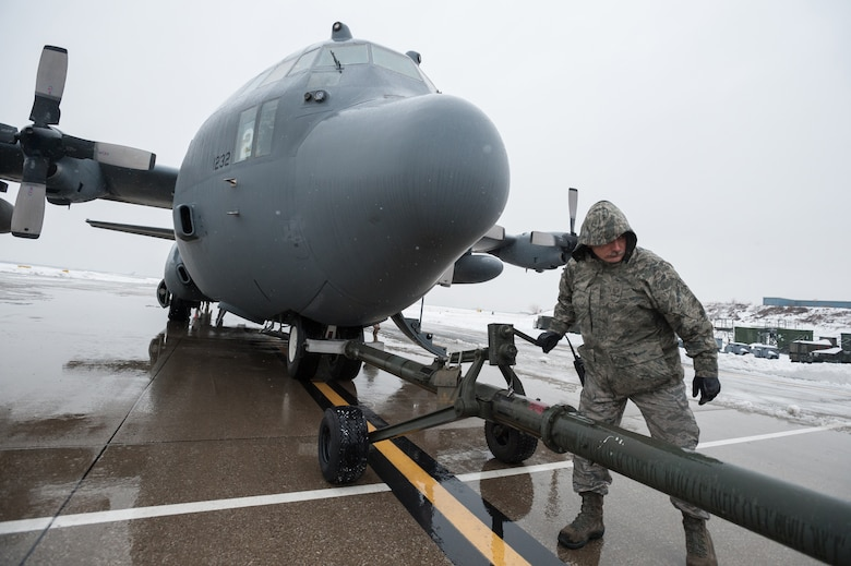 Master Sgt. Carl Shaffer, a C-130 crew chief in the 123rd Aircraft Maintenance Squadron, works to disconnect a tow bar from a C-130 Hercules aircraft on the flight line of the Kentucky Air National Guard Base in Louisville, Ky., Feb. 21, 2015. The aircraft, which subsequently departed for the Persian Gulf along with 37 deploying Kentucky Air Guardsmen, was being housed in a hangar because of severe weather conditions. (U.S. Air National Guard photo by Maj. Dale Greer)