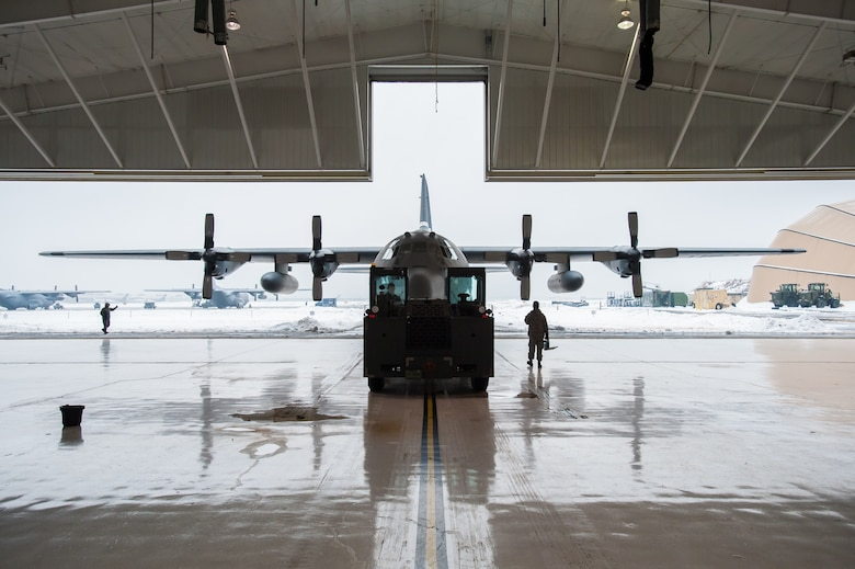 Members of the 123rd Aircraft Maintenance Squadron push a C-130 Hercules aircraft from a hangar at the Kentucky Air National Guard Base in Louisville, Ky., Feb. 21, 2015. The aircraft, which subsequently departed for the Persian Gulf along with 37 deploying Kentucky Air Guardsmen, was being housed in the hangar because of severe weather conditions. (U.S. Air National Guard photo by Maj. Dale Greer)