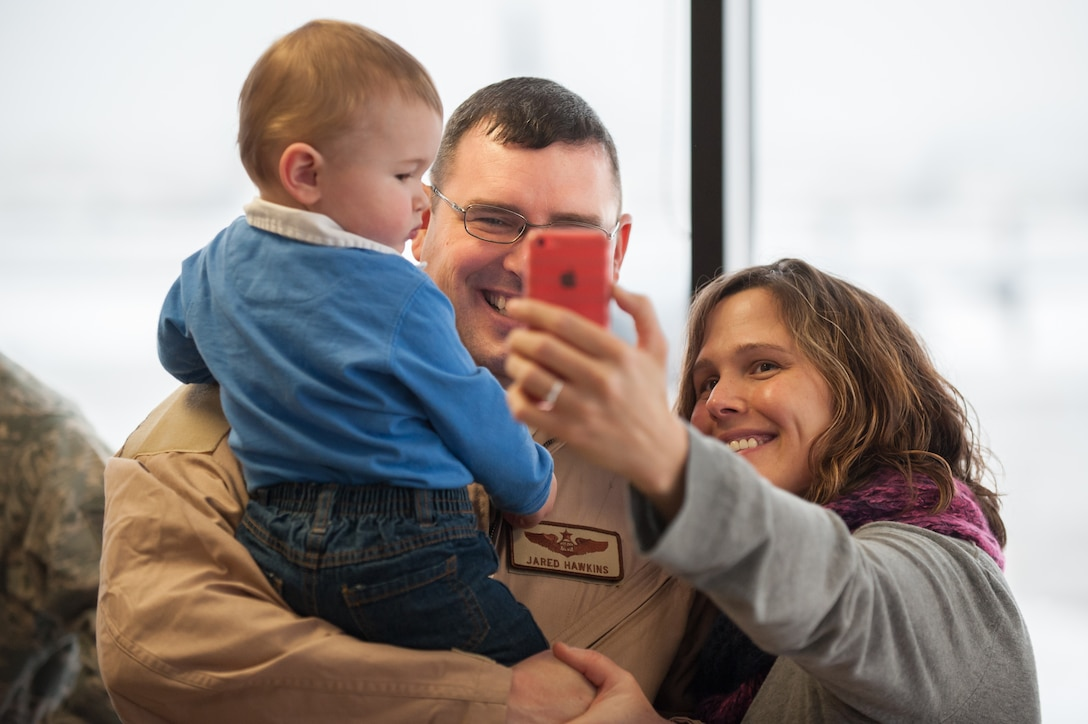 Maj. Jared Hawkins, a C-130 Hercules navigator in the 123rd Airlift Wing, poses for a selfie with his son and wife, Jaime and Lairkin Hawkins, at the Kentucky Air National Guard Base in Louisville, Ky., Feb. 21, 2015. Hawkins is deploying to the Persian Gulf in support of Operation Freedom's Sentinel, during which more than 110 members of the Kentucky Air Guard will fly troops and cargo across the U.S. Central Command Area of Responsibility. (U.S. Air National Guard photo by Maj. Dale Greer)