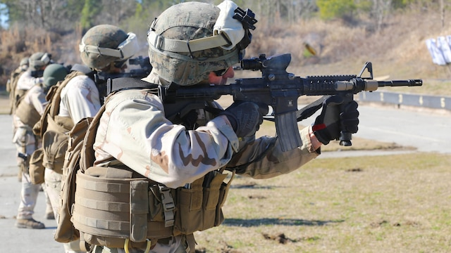A Marine with 2nd Combat Engineer Battalion, 2nd Marine Division, fires an M4 carbine rifle at a range here, Feb. 10, 2015. Critical Skills Operators with 3rd Marine Special Operations Battalion, U.S. Marine Corps Forces Special Operations Command, trained with 2nd CEB Marines during RAVEN 15-03, a 10-day realistic military training exercise to enhance 3rd MSOB's readiness for worldwide support to global security. Marines with 2nd CEB played the role of a partner nation force during the exercise.