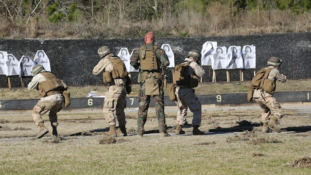 A Critical Skills Operator with 3rd Marine Special Operations Battalion, U.S. Marine Corps Forces Special Operations Command, watches as Marines with 2nd Combat Engineer Battalion, 2nd Marine Division, fire M4 carbine rifles at a range here, Feb. 10, 2015. Marines with 3rd MSOB participated in RAVEN 15-03, a 10-day realistic military training exercise to enhance the battalion's readiness for worldwide support to global security. Marines with 2nd CEB played the role of a partner nation force during the exercise.