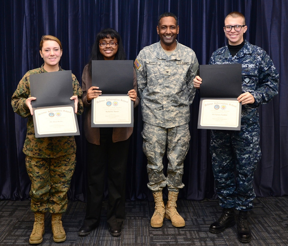 Col. Jeremy Martin, Defense Information School commandant, presents certificates to the winners of the Martin Luther King, Jr. poetry contest to Pfc. Alexis Rocha, DINFOS student and second place winner, Rachel M. Martin, a Fort Meade High School student and third place winner, and Seaman Zackary Landers, DINFOS student and first place winner, Fort Meade, Md., Jan. 28, 2015. The observance, hosted by the DINFOS Equal Opportunity committee, provided music, poetry and education for service members and civilians at the school. (DoD photo by Staff Sgt. David Chapman/Released)