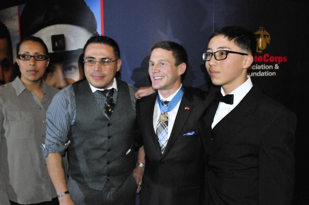 Medal of Honor recipient William Kyle Carpenter, center, who was the Guest of Honor at Friday night's Marjah Marines Reunion Dinner at the National Museum of the Marine Corps, poses for a picture with Gunnery Sgt. Matt Mata, left, and his 13-year-old son, Erin. Matt Mata served in Marjah as a staff sergeant with the 1st Battalion, 6th Marine Regiment.