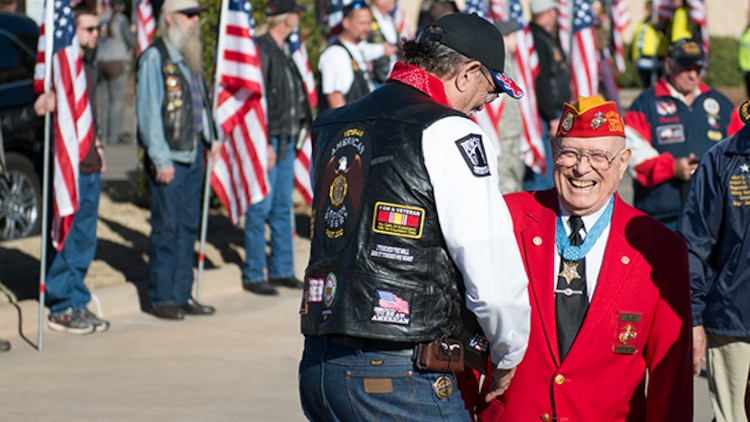 """Hershel """"Woody"""" Williams, Marine survivor from the battle of Iwo Jima and the last living Medal of Honor recipient for his actions during the battle, walks past Patriot Guard Riders who lined the walkway from the hotel to the Wellington Center where events were held during the Iwo Jima Battle Survivors and Family Association 70th anniversary reunion at Wichita Falls, Texas, February 14, 2015. Survivors and their families gathered for four days to share remeberances and commeraderie, and to remember and honor the service members who died during the battle and survivors who have died."""