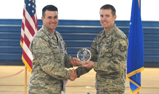 Col. John Wagner, 460th Space Wing commander, presents the Maj. Gen. Eugene A. Lupia Award to Tech. Sgt. Gregory M. Whittet, 460th Civil Engineering Squadron acting first sergeant, Feb. 19, 2015, at Buckley Air Force Base, Colo. Whittet received the award for his job performance and leadership. (U.S. Air Force photo by Airman 1st Class Luke W. Nowakowski/Released)