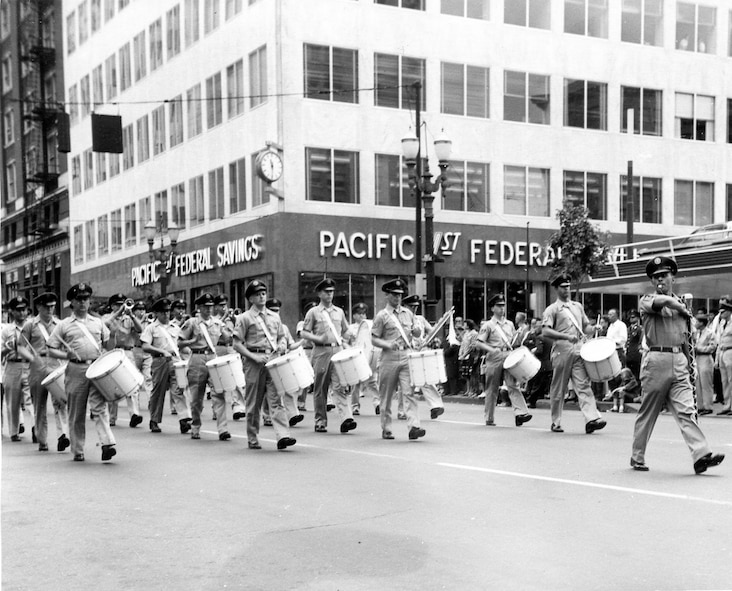 The OreANG's Twirler, probably champion Ms. Carol Johnson, leads the OreANG Drum & Bugle Corps in the summer khaki uniforms of that era down a Portland street in the 53rd Annual Rose Festival's Grand Floral Parade, Saturday, June 10, 1961. Drum Major MSgt Unverricht leads the corps immediately behind her.
