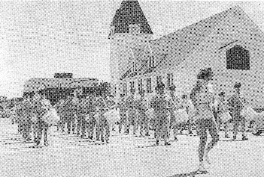 The Twirler leads the OreANG Drum & Bugle Corps through Astoria, Oregon during the Astoria Regatta Parade of Aug. 26, 1961. The corps won Best Performing Drum & Bugle Corps.