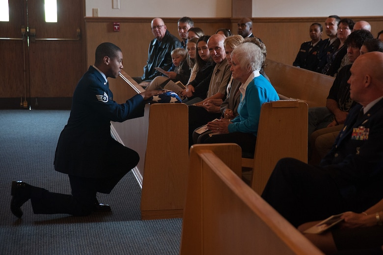 """U.S. Air Force Staff Sgt. Craig A. McBean, Jr., executive assistant to the Command Chief, 14th Air Force presents an American flag to Betty Flynn during a memorial service for her daughter, Tammy Martin, Feb. 19, 2015, at the base chapel.  The 14th Air Force Commander's Secretary since 1998, """"Ms. Tammy,"""" as she was known, was celebrating her 40th year as a civil servant at the time of her passing from a sudden illness, Feb. 12, 2015.  (U.S. Air Force photo by Michael Peterson/Released)"""