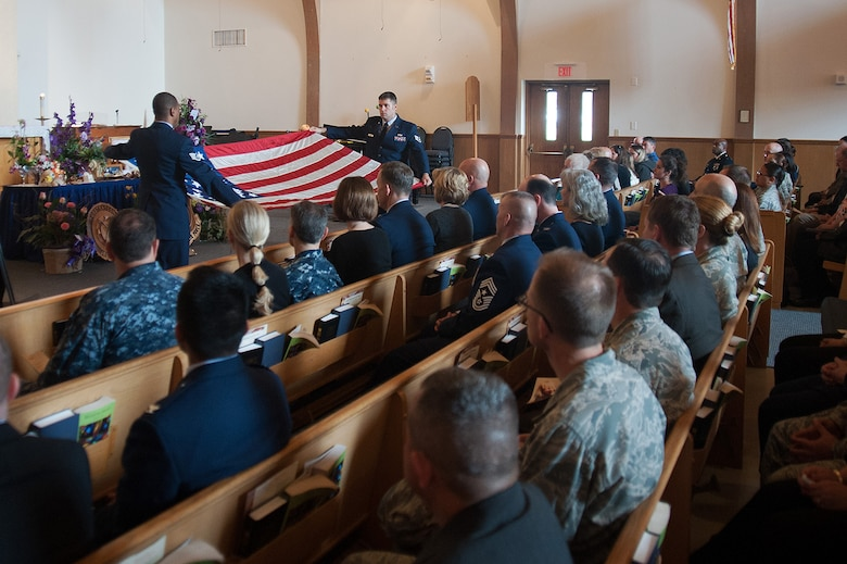 """Members of 14th Air Force perform a flag-folding ceremony during a memorial service for Tammy Martin, 14th Air Force Commander's Secretary, at the base chapel, Feb. 19, 2015.  A 40-year civil servant, """"Ms. Tammy,"""" as she was known, passed away Feb. 12, 2015 following a sudden illness. More than 200 friends, family members and members of her extended Air Force family were on hand to celebrate her life.  (U.S. Air Force photo by Michael Peterson/Released)"""