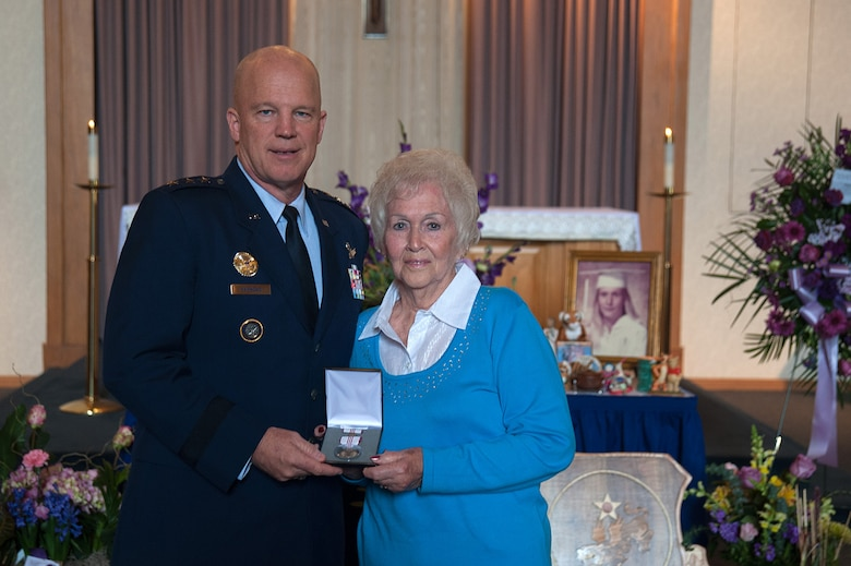 """U.S. Air Force Lt. Gen. Jay Raymond, commander, 14th Air Force (Air Forces Strategic) and Joint Functional Component Command for Space, presents the Outstanding Civilian Career Service Award to Betty Flynn during a memorial service for her daughter, Tammy Martin, Feb. 19, 2015, at the base chapel.  The 14th Air Force Commander's Secretary since 1998, """"Ms. Tammy,"""" as she was known, was celebrating her 40th year as a civil servant at the time of her passing from a sudden illness, Feb. 12, 2015.  (U.S. Air Force photo by Michael Peterson/Released)"""