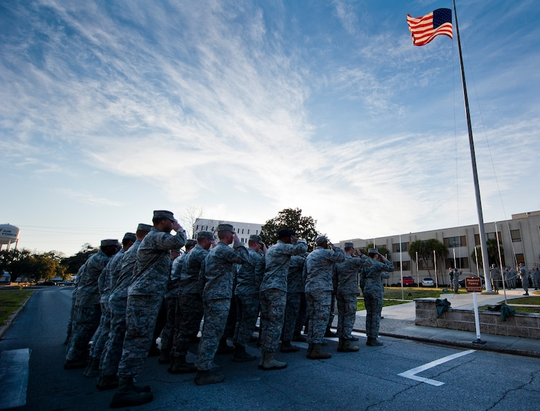 A formation of Airmen salute as the base flag is lowered during a retreat ceremony Feb. 19 at Eglin Air Force Base, Fla.  The ceremony was held a week early in honor of Black History Month.  (U.S. Air Force photo/Samuel King Jr.)