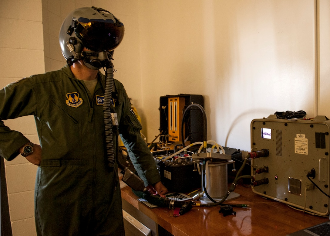 Col. Scott Thompson, 96th Operations Group commander, checks the fit of his Joint Helmet Mounted Cueing System visor at the Aircrew Flight Equipment facility on Eglin Air Force Base, Fla., Feb. 9.  The JHMCS is a modified HGU-55/P helmet that incorporates a visor projected Heads-Ups Display to cue weapons and sensors to the target. The maintenance of the helmets is critical to the pilot's performance and safety.  (U.S. Air Force photo/Ilka Cole)