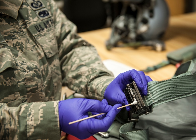 Staff Sgt. Karol Carmona, of the 96th Operations Support Squadron, applies lubricant with a cotton swab to the ejection seat release fittings on a flight torso harness at the Aircrew Flight Equipment facility on Eglin Air Force Base, Fla., Feb. 9. AFE technicians perform pre and post flight inspections of the torso harnesses.  In addition, the torso harnesses receive additional inspections and lubrication every 180 days.  The torso harness is the connection point between the aircrew member and their parachute.  (U.S. Air Force photo/Ilka Cole)