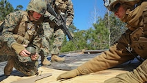 Marines with 2nd Combat Engineer Battalion set up an explosive charge on a rooftop during their urban breaching training exercise on Engineer Training Area-1 aboard Marine Corps Base Camp Lejeune, N.C., Feb. 19, 2015. During the training, the unit learned how to open any type of door, gate or roof using a variety of tools, from explosives to shotguns and sledge hammers. They learned to do whatever was necessary to allow the infantry squad they were supporting to enter the building.