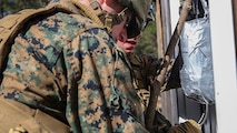 Two Marines with 2nd Combat Engineer Battalion set up an explosive charge that will blast open the locked door during their urban breaching training exercise on Engineer Training Area-1 aboard Marine Corps Base Camp Lejeune, N.C., Feb. 19, 2015. During the training, the unit learned how to open any type of door, gate or roof using a variety of tools, from explosives to shotguns and sledge hammers. They learned to do whatever was necessary to allow the infantry squad they were supporting to enter the building.