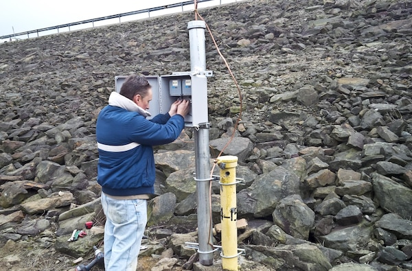 Joe Premozic works to adjust dataloggers in the newly installed permanent enclosure for piezometers at Crooked Creek Dam