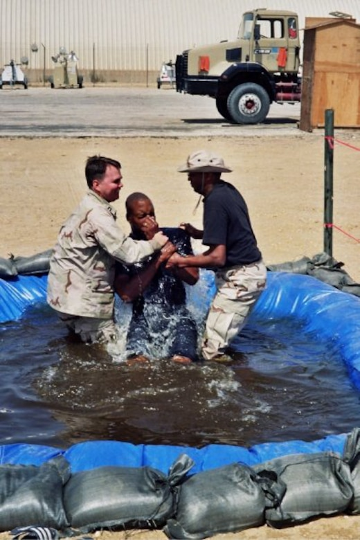 (Then) Capt. Matthew Boyd (left) baptizes a service member during a deployment to the Middle East in 2009. Now a major, Boyd continues his long lineage of serving in the military as a chaplain offering guidance and contentment for those in need. (Courtesy photo)