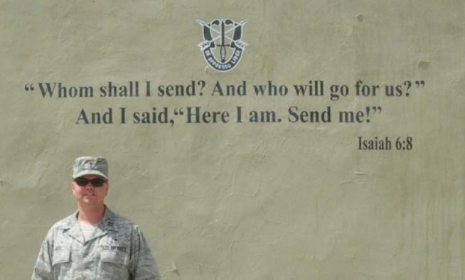 Then Capt. Matthew Boyd stands next to the motto of a special operations unit he deployed with in 2009 as their chaplain in the Middle East. Now a major, Boyd joined the Air Force and pursued his passion in religion after finishing his career as a howitzer cannon crew member for the Army Reserve. (Courtesy photo)