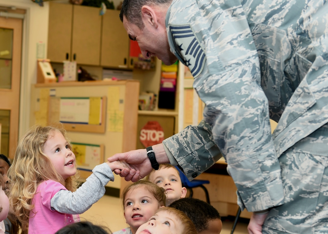 Chief Master Sgt. Brian Kruzelnick, 460th Space Wing command chief, shakes a child's hand before reading to the class Feb. 24, 2015, at the A-Basin Child Development Center on Buckley Air Force Base, Colo. The wing leader read to the class in honor of Black History Month. (U.S. Air Force photo by Airman 1st Class Samantha Saulsbury/Released)
