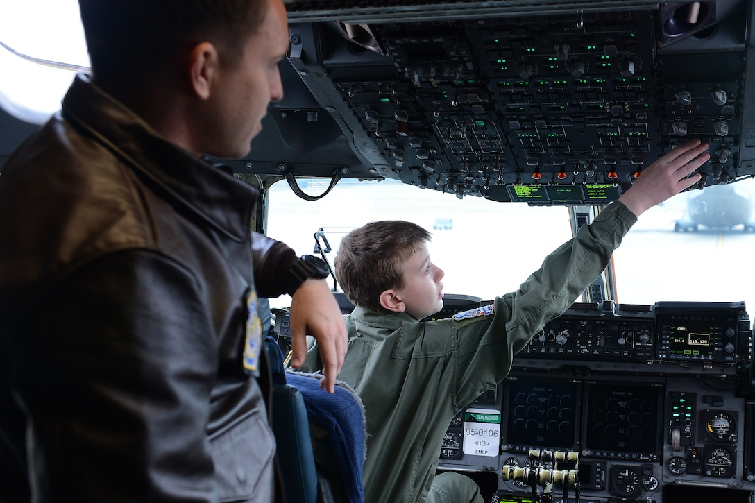 Carver Faull (right) explores the  buttons in the cockpit of a C-17 Globemaster III with 1st Lt. Brit Reuscher, 4th Airlift Squadron C-17 pilot, at Joint base Lewis-McChord, Wash. Feb. 20, 2015. Carver spent the day with members of McChord Field as part of the Pilot for a Day Program. (U.S. Air Force photo/Staff Sgt. Tim Chacon)
