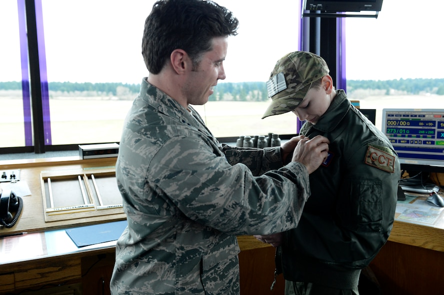Carver Faull, Team McChord's Pilot for a Day, receives his Air Traffic Control badge from Capt. Steven Young, 62nd Operations Squadron air field operations flight commander, Feb. 20, 2015, at Joint Base Lewis-McChord, Wash. Carver was recognized as an honorary air traffic controller at McChord Tower and was given his own call sign. (U.S. Air Force photo/Senior Airman Rebecca Blossom)