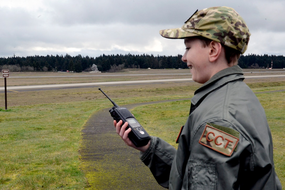 Carver Faull, a participant in the Pilot for a Day program on McChord Field, smiles after members of the 627th Civil Engineer Squadron's explosive ordinance disposal team let him make the call to detonate explosives, Feb. 20, 2015, at Joint Base Lewis-McChord, Wash. After Carver called the detonation over the radio, two and a half pounds of C-4 ignited from across the air field. (U.S. Air Force photo/Senior Airman Rebecca Blossom)